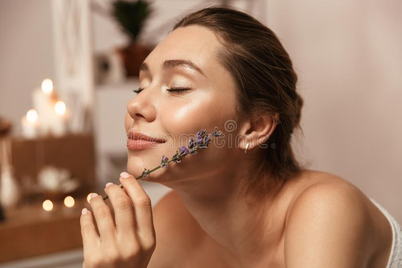 Beautiful woman lies in bathroom over candles holding lavender. stock images