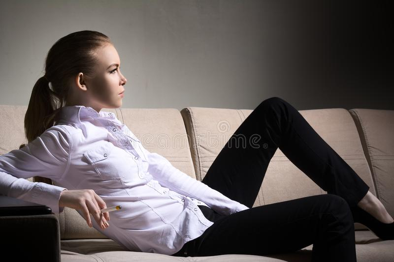 Beautiful woman lies on the couch and smokes a cigarette. Courageous woman stock photos