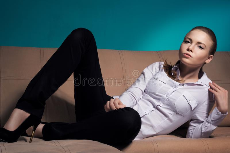 Beautiful woman lies on the couch and smokes a cigarette. Courageous woman stock photography