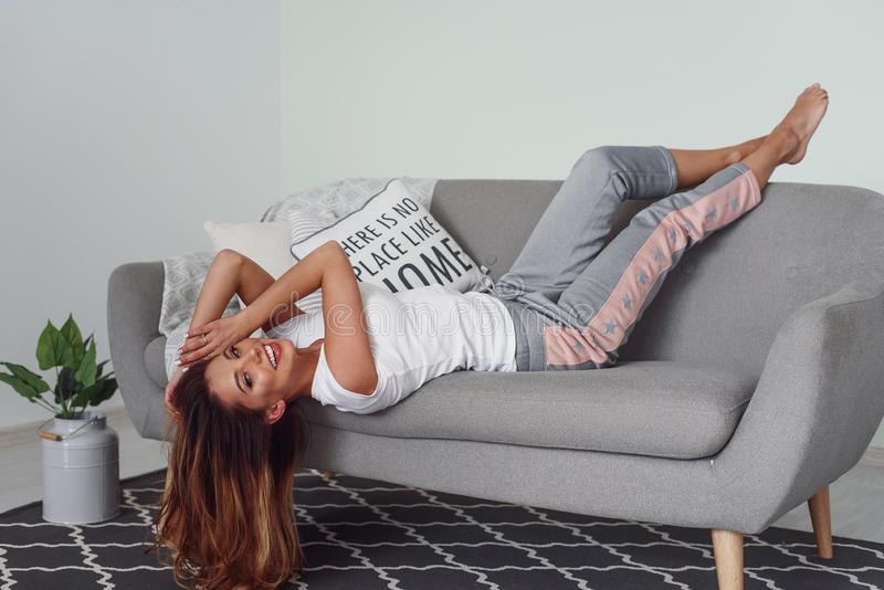 Beautiful woman relaxing on a grey couch with head upside down. Cute girl having fun at cozy home in lazy day. A beautiful woman lies on a grey couch with royalty free stock images