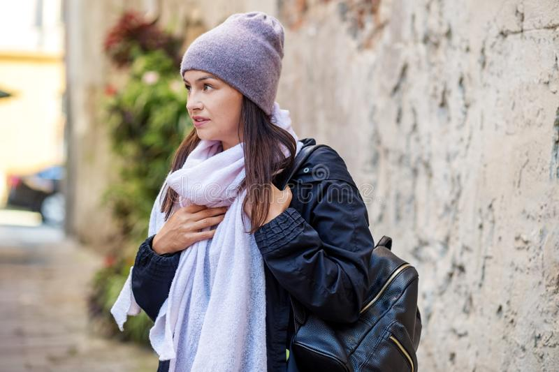 Beautiful woman in a light purple knitted hat and scarf. Concept lifestyle, autumn, urban stock photography