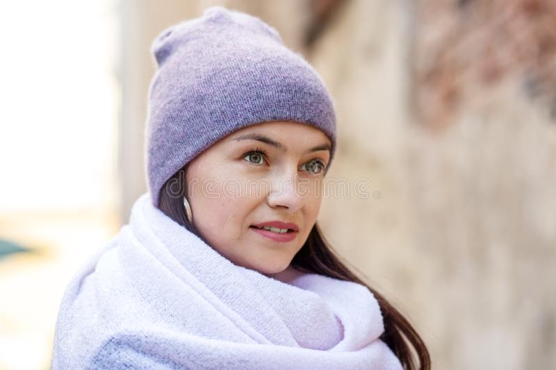 Beautiful woman in a light purple knitted hat and scarf. Concept lifestyle, autumn, urban stock images