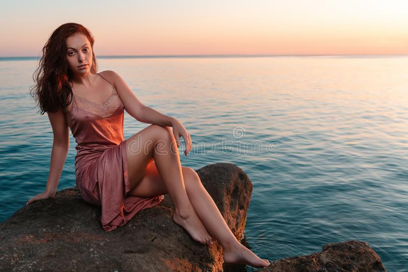 Beautiful woman in lingerie posing on a coastal cliff. Sea and sunset in the background. Copy space stock photos