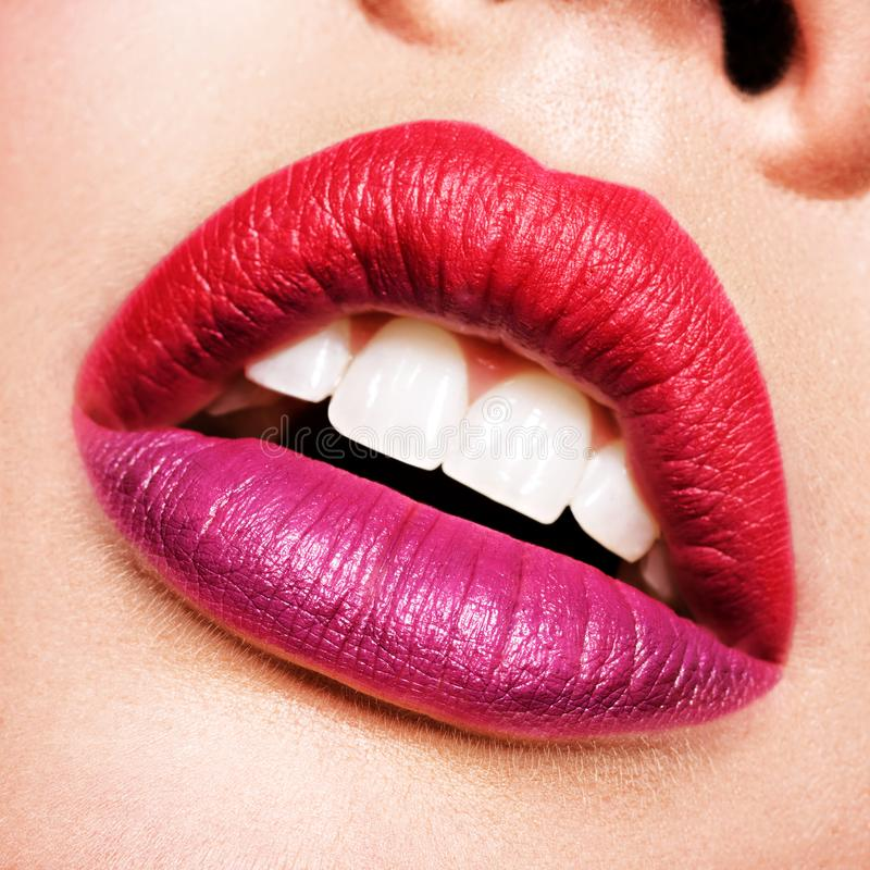 Beautiful woman lips with  red and purple lipstick stock images