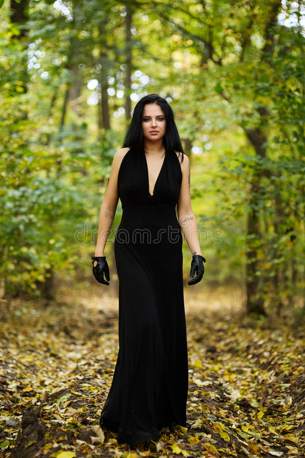 Beautiful woman with long black dress in the forest royalty free stock image