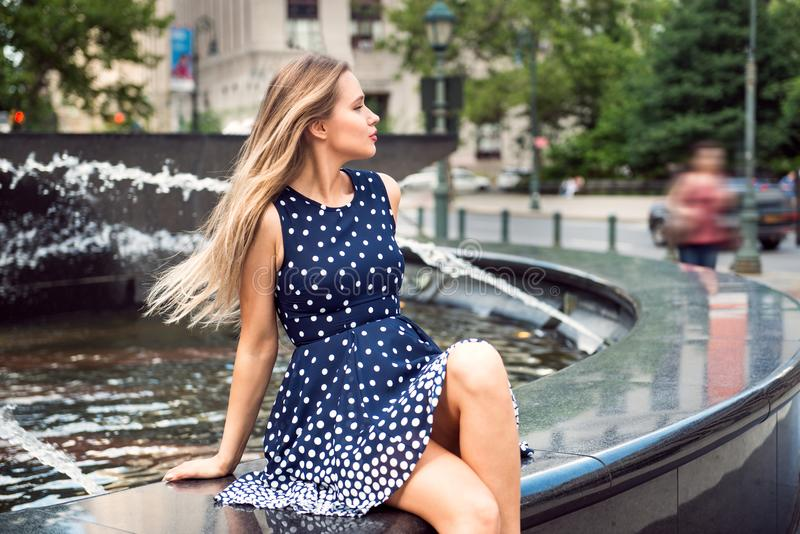 Beautiful woman with long blond hair sitting in the city park at summer time. royalty free stock photography