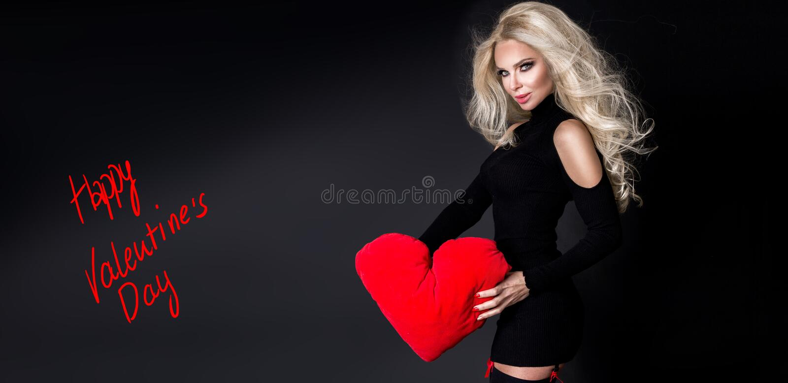 Beautiful woman with long blond hair standing on a black background dressed in red underwear and holds in his hands. A red heart Valentine`s Day stock images