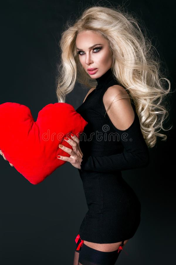Beautiful woman with long blond hair standing on a black background dressed in red underwear and holds in his hands. A red heart Valentine`s Day stock photo