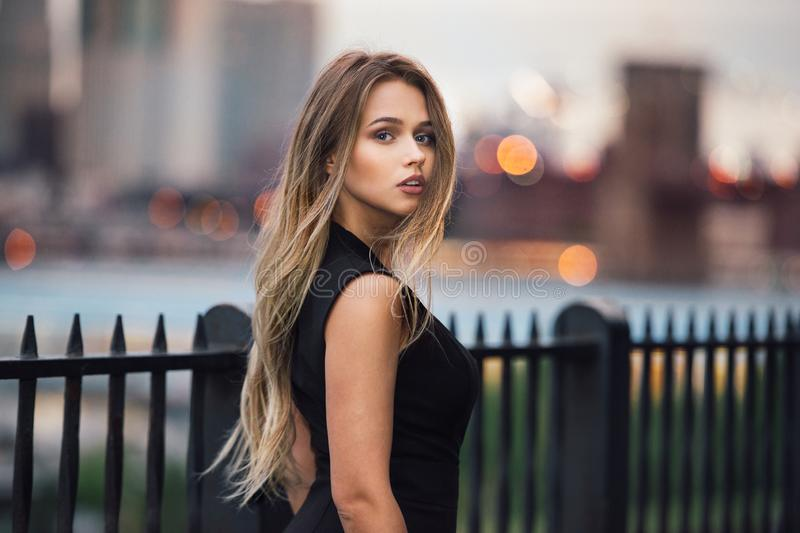 Beautiful woman with long blond hair walking in the city at evening time wearing elegant black dress. stock photos