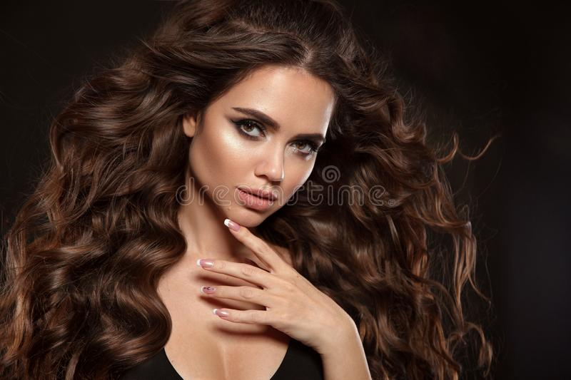 Beautiful woman with long brown curly hair. Closeup portrait with a pretty face of the young girl. Fashion model with manicure royalty free stock photo