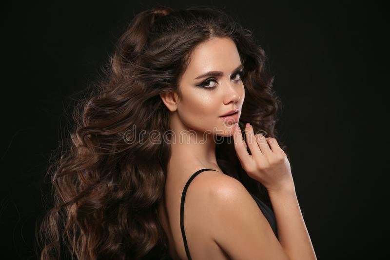 Beautiful woman with long brown curly hair. Closeup portrait with a pretty face of the young girl. Jewelry store copyscpace. stock photos