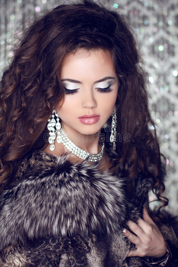 Beautiful woman with long brown hair in luxury fur coat. Closeup stock images