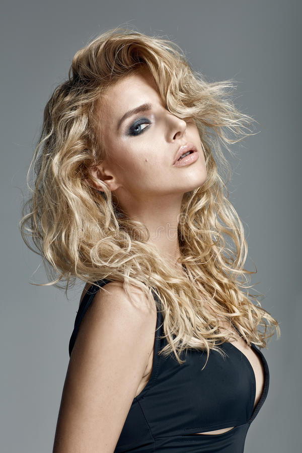Beautiful woman with long curly blond hair royalty free stock image