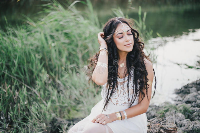 Beautiful woman with long curly hair dressed in boho style dress posing near lake stock images