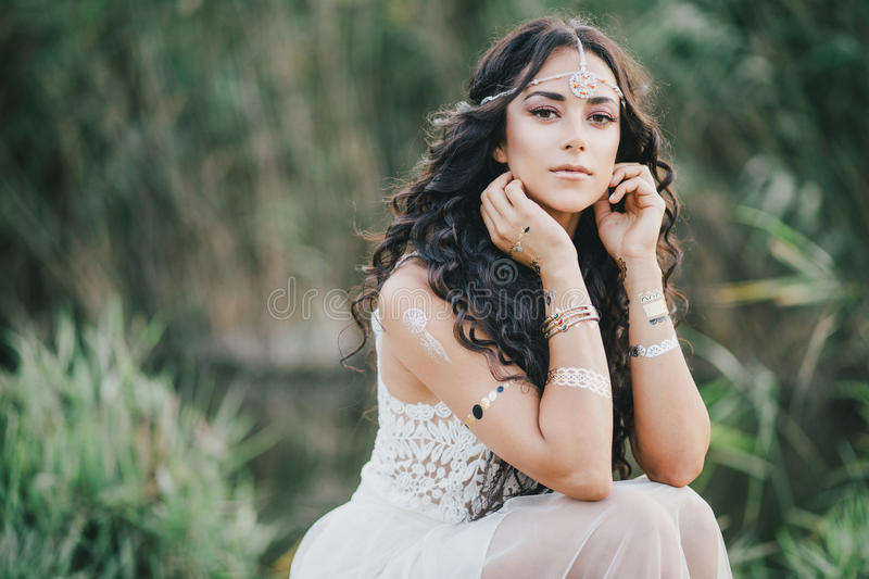 Beautiful woman with long curly hair dressed in boho style dress posing near lake stock photo