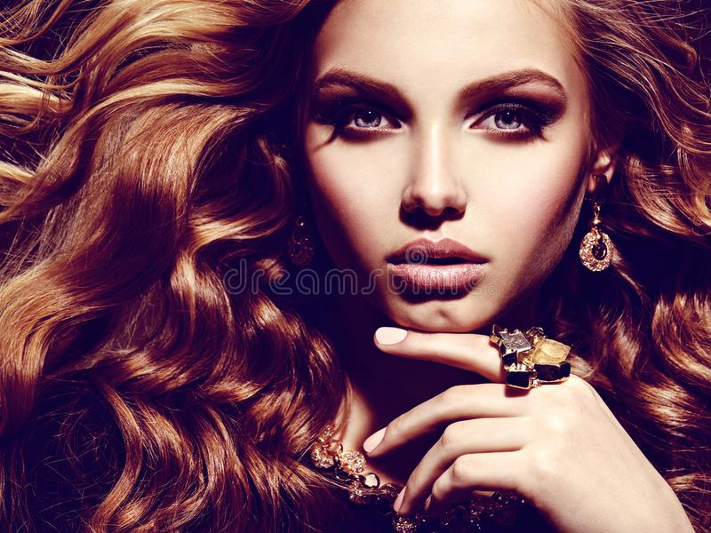 Beautiful woman with long curly hair and gold jewelry stock photography