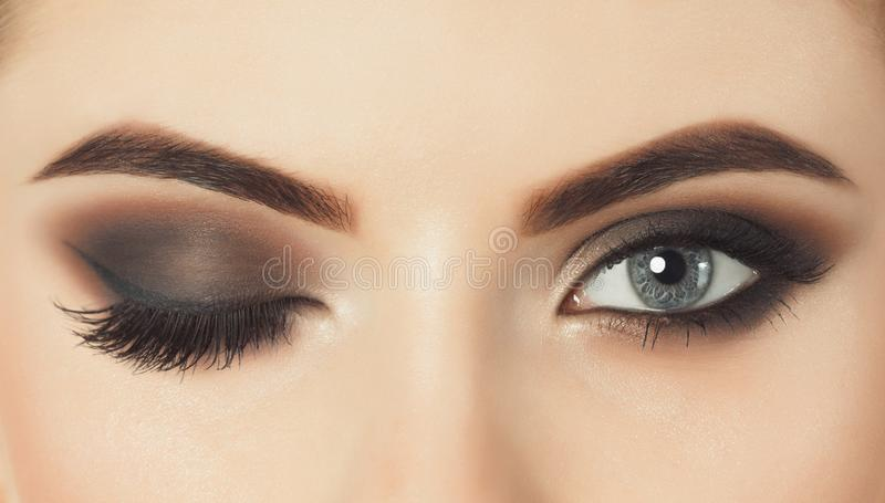 Beautiful woman with long eyelashes and with beautiful evening make-up. Eyes close up.One eye is closed and the other is open royalty free stock photos