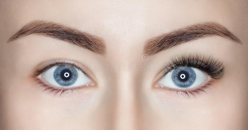 A beautiful woman with long eyelashes in one eye, and on the other, eyelashes are not extended. Eyes close up.  royalty free stock image