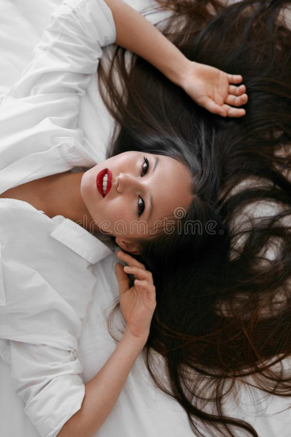 Beautiful woman with long hair, red lips makeup in white shirt. Beautiful asian woman with long healthy hair and red lips makeup in white shirt lying on bed stock image