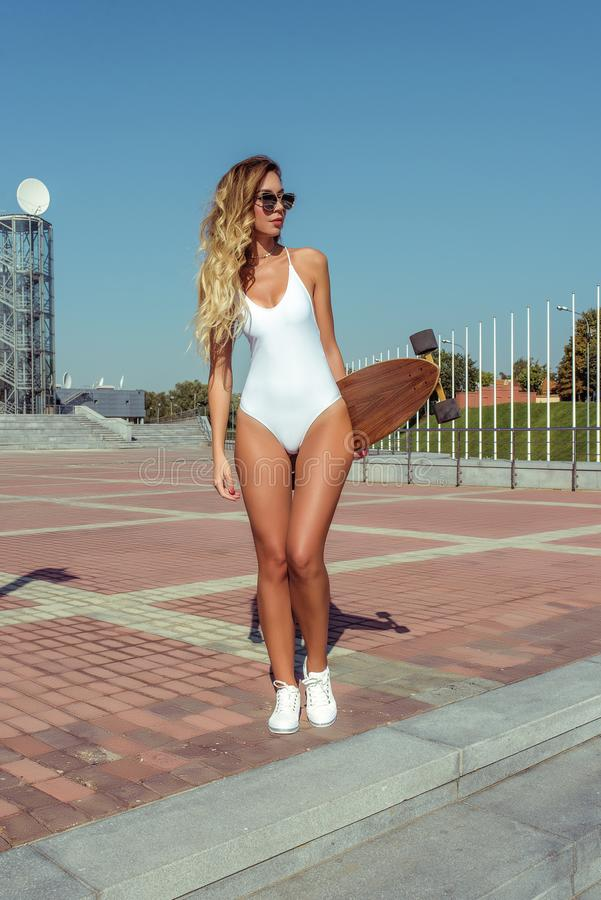 Beautiful woman long hair skate board, longboard, girl summer in city. White bodysuit swimsuit glasses sneakers. Concept royalty free stock images