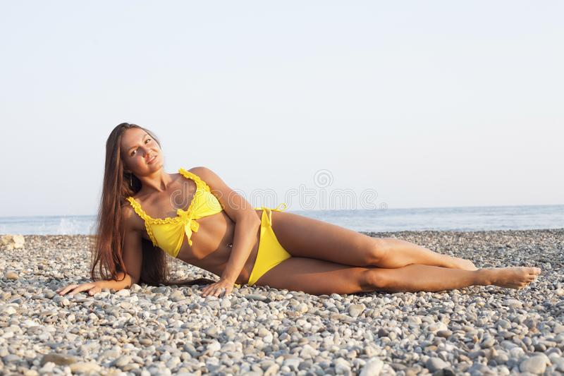 Beautiful woman with long hair in yellow swimsuit sunbathes on the beach. Beautiful woman with long hair in yellow swimsuit sunbathes stock photo