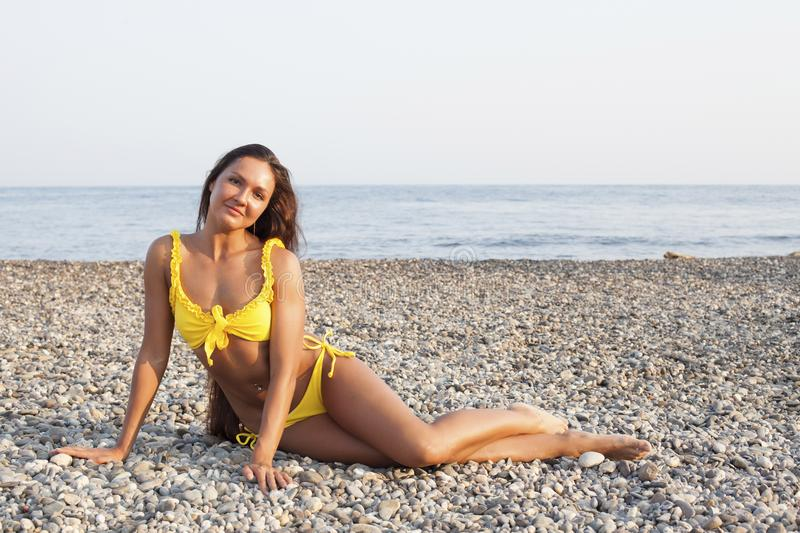 Beautiful woman with long hair in yellow swimsuit sunbathes on the beach. Beautiful woman with long hair in yellow swimsuit sunbathes royalty free stock image