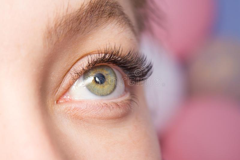 Beautiful Woman with long lashes in a beauty salon. Eyelash extension. Eyelash Extension Procedure. Woman Eye with Long false Eyelashes. Close up macro shot of stock photo