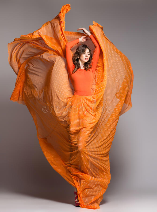 Beautiful woman in long orange dress posing dramatic. Beautiful woman in long orange dress blowing in the wind posing dramatic in the studio on grey background royalty free stock photo