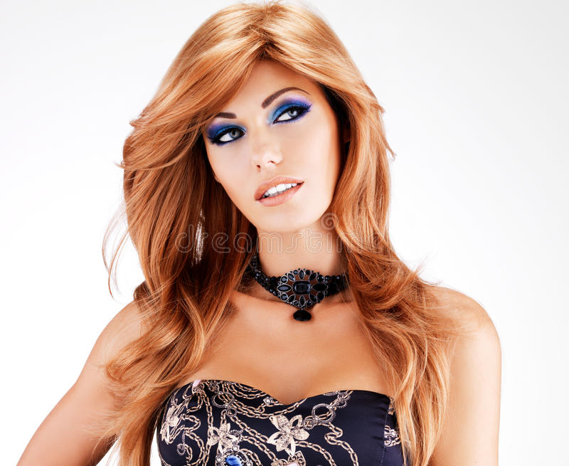 Beautiful woman with long red hairs with blue makeup royalty free stock photography