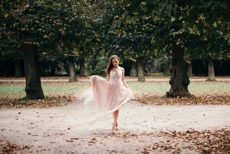 Beautiful woman in long rose evening dress walking path in park. royalty free stock photos