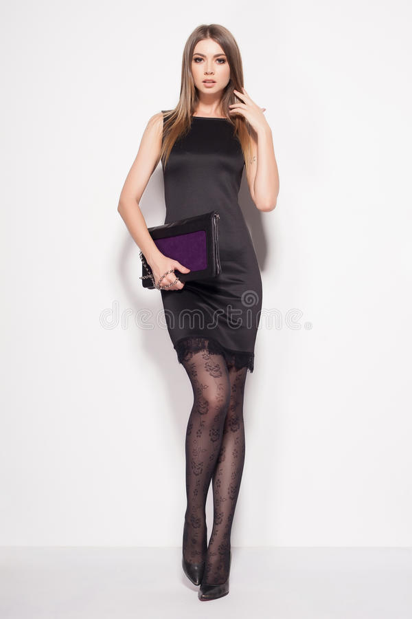 Beautiful woman with long legs dressed elegant posing in the studio stock images