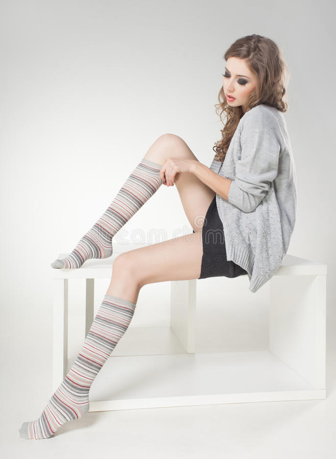 Beautiful woman with long legs in winter socks posing in the studio stock images