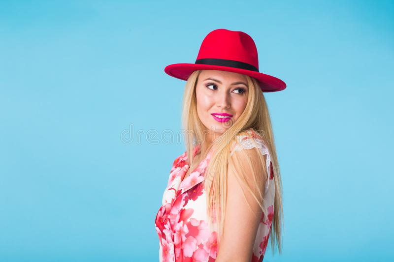 Beautiful woman with long straight blond hair. Fashion model posing at studio on blue background with copyspace stock images