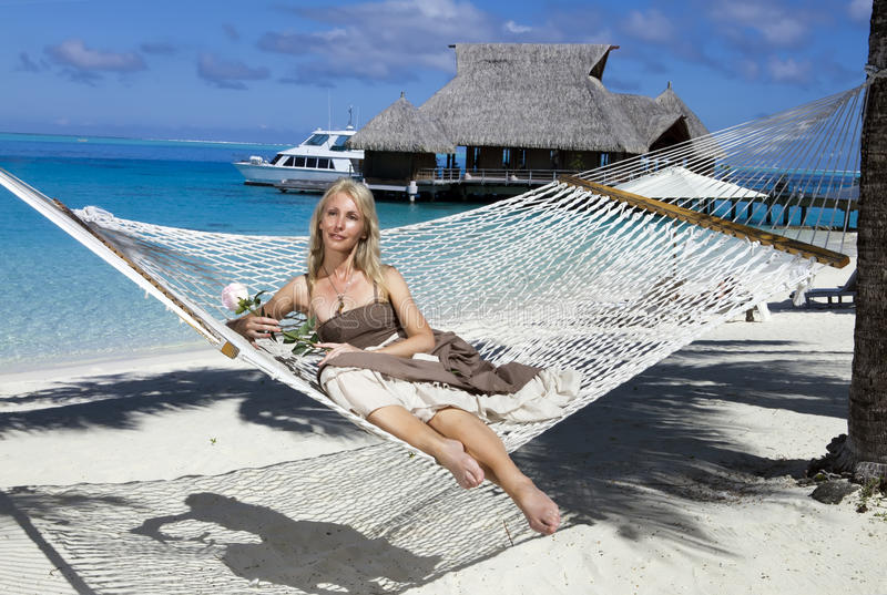 The beautiful woman in a long sundress in a hammock on a sea background royalty free stock photo