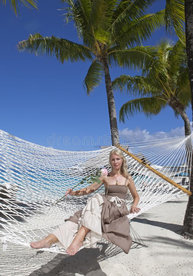 beautiful woman in a long sundress in a hammock on a sea background stock photos