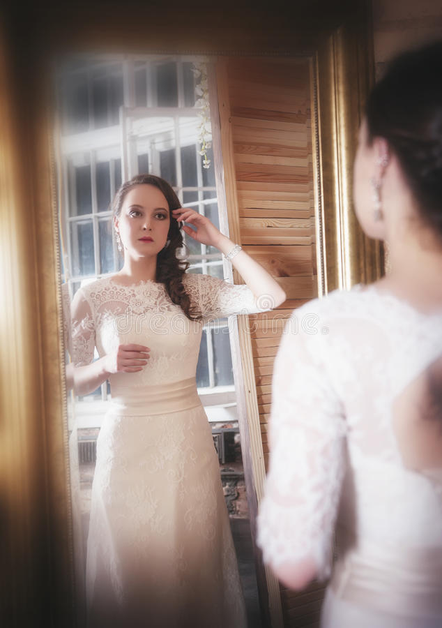 Beautiful woman in long wedding dress looking in mirror stock photography