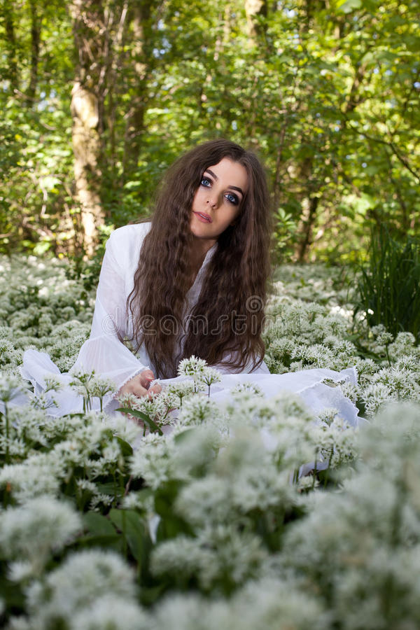 Beautiful woman in long white dress sitting in a forest stock photos