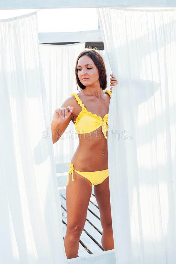 Beautiful woman with long in yellow swimsuit on the beach. Woman with long in yellow swimsuit on the beach stock photos