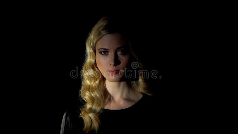 Beautiful woman looking at camera against dark background, femininity concept royalty free stock image