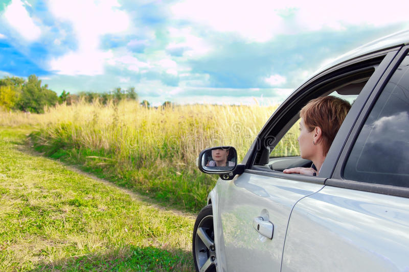Beautiful woman looking from the car royalty free stock image