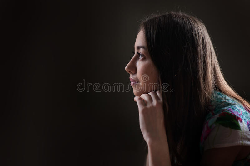 Beautiful woman looking into the distance on a dark background royalty free stock photography