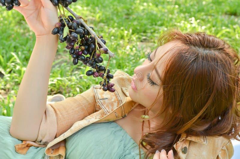 Beautiful woman looking at fruit stock photography