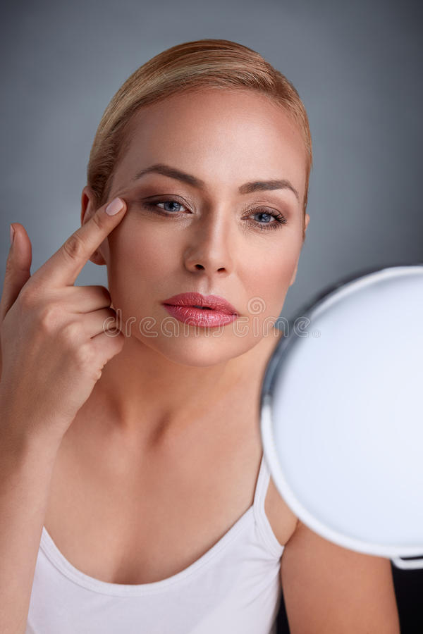 Beautiful woman looking her wrinkles in mirror royalty free stock images