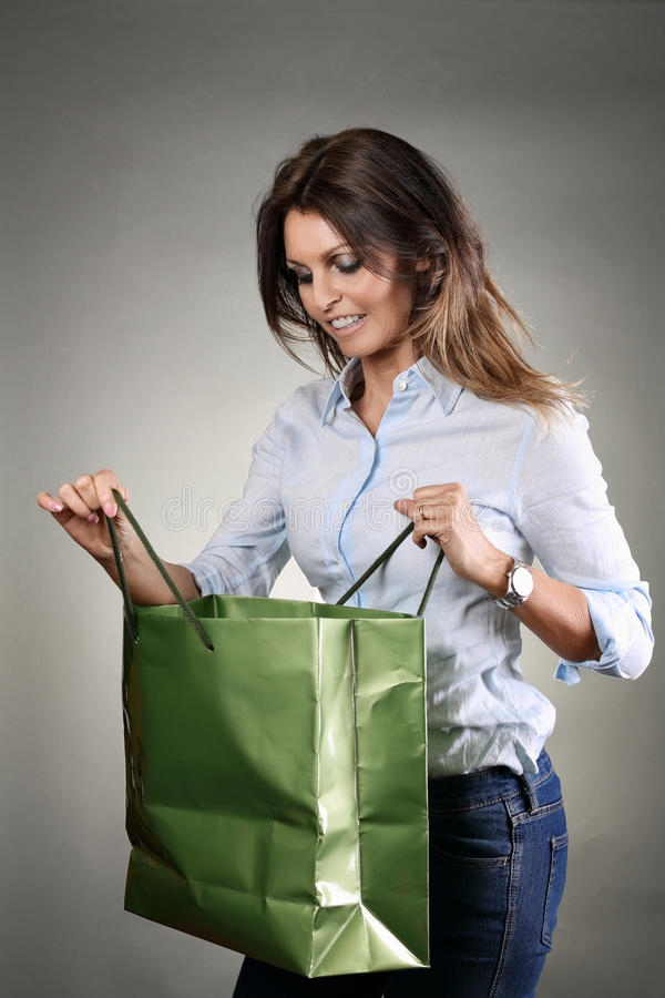 Beautiful woman with looking inside shopping bag stock images