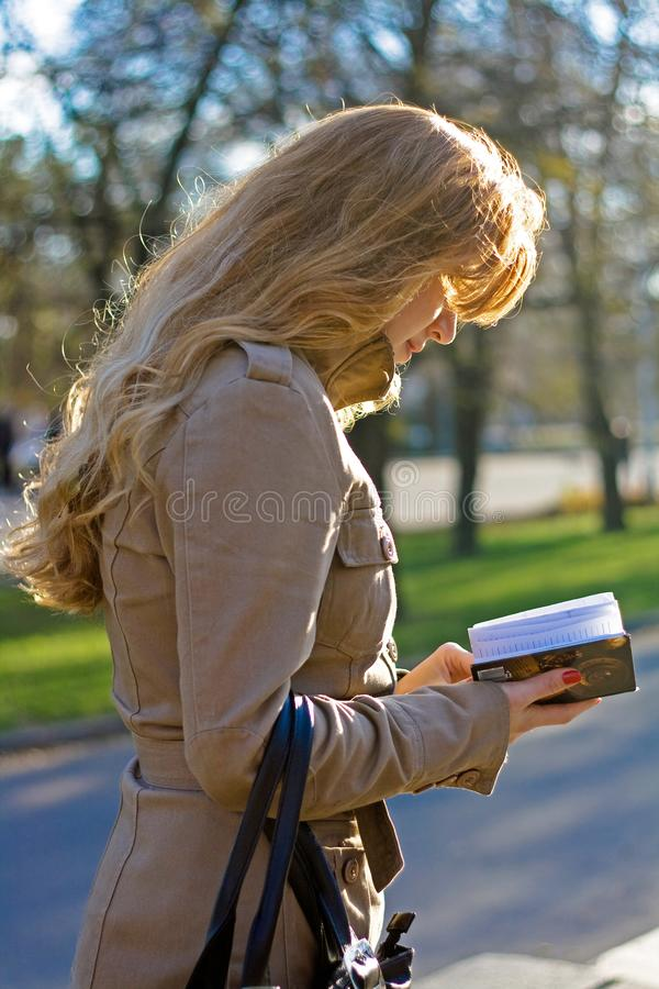 Beautiful woman looking in paper notebook in the park stock photo