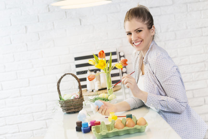 Beautiful woman looking at a tablet and coloring eggs stock images