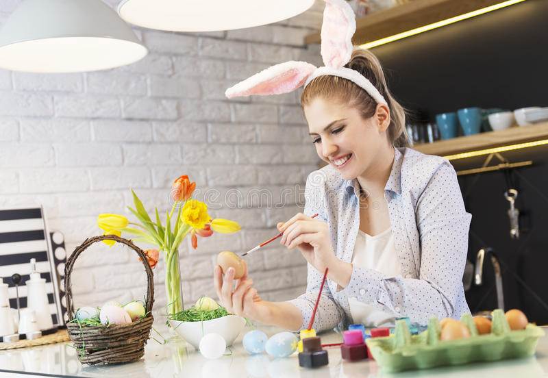 Beautiful woman looking at a tablet and coloring eggs royalty free stock photography