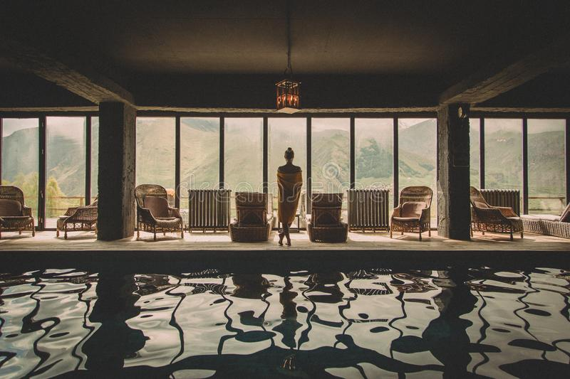 Beautiful woman looking to the view of mountains in the rooms with swimming pool and panoramic windows stock photo