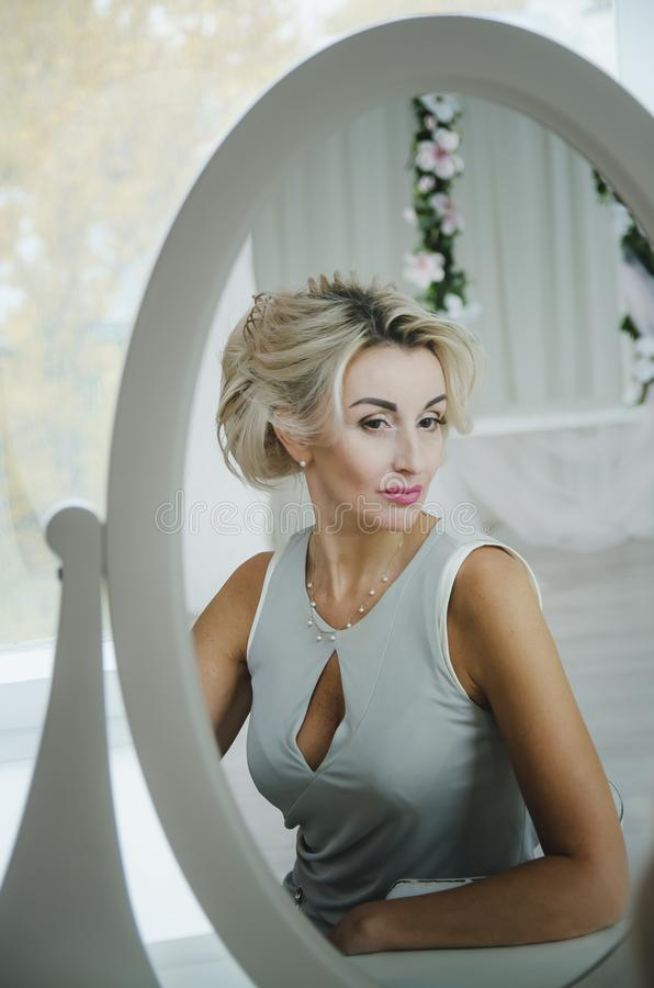 A beautiful woman looks in the mirror royalty free stock image
