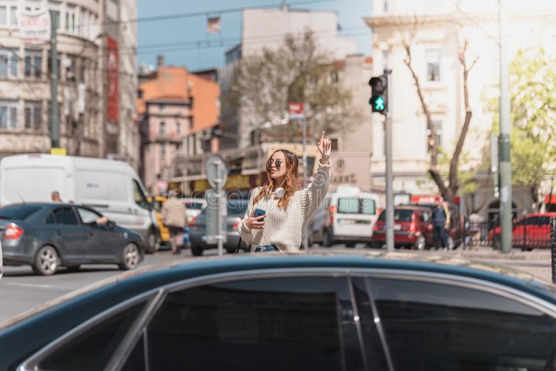 Beautiful woman looks for a taxi at street. Beautiful attractive young girl in jumper and jeans with headphones,sunglasses and smartphone looks for a taxi at royalty free stock images